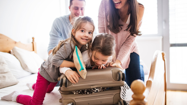 Family trying to close a suitcase