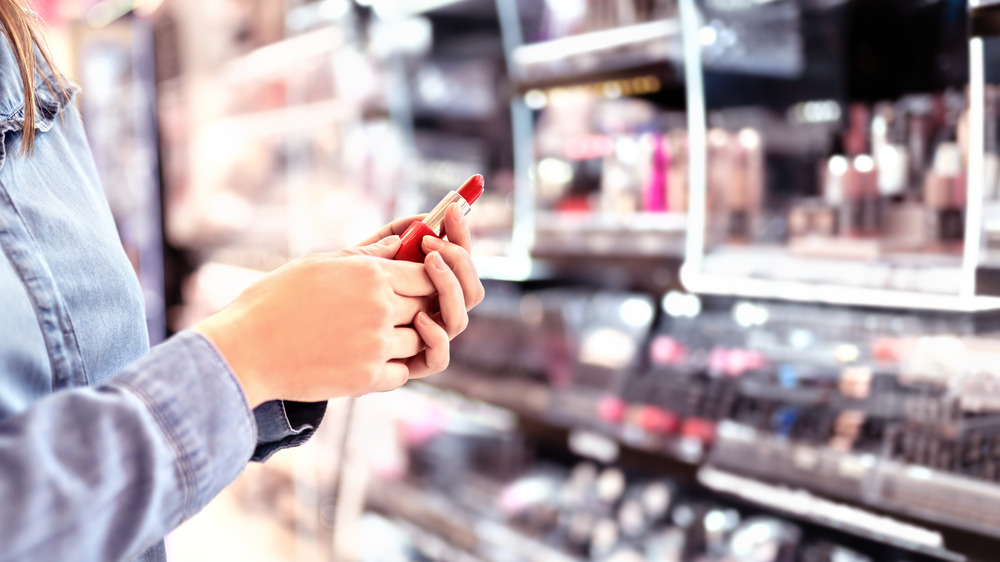 Person selecting lipstick a makeup store