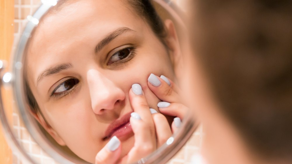 Woman looking at her pimples