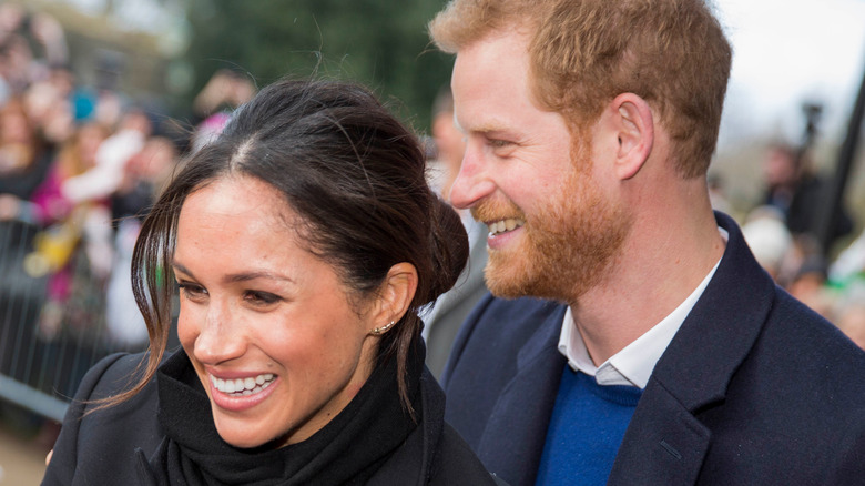 Prince Harry and Meghan Markle smiling in a crowd