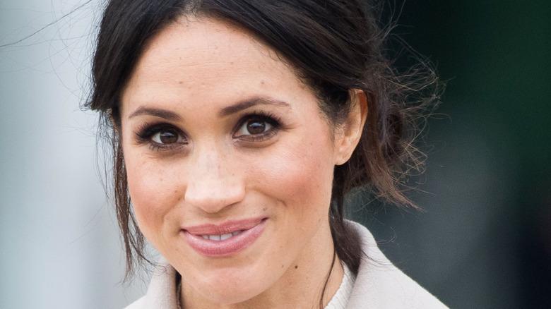 Meghan Markle smiling in a beige coat