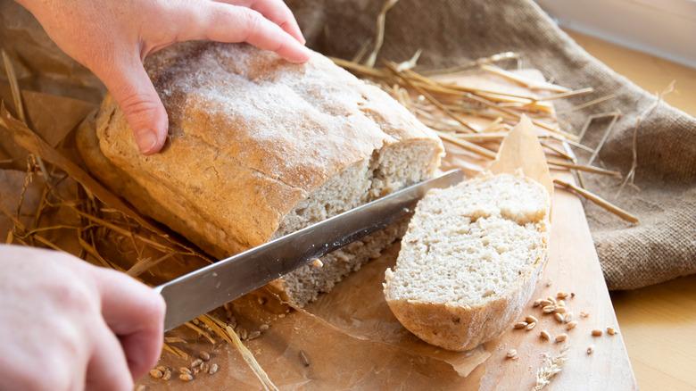Person slicing bread