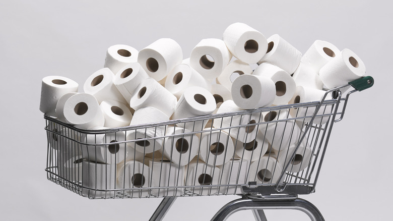 toilet paper piled into a shopping cart