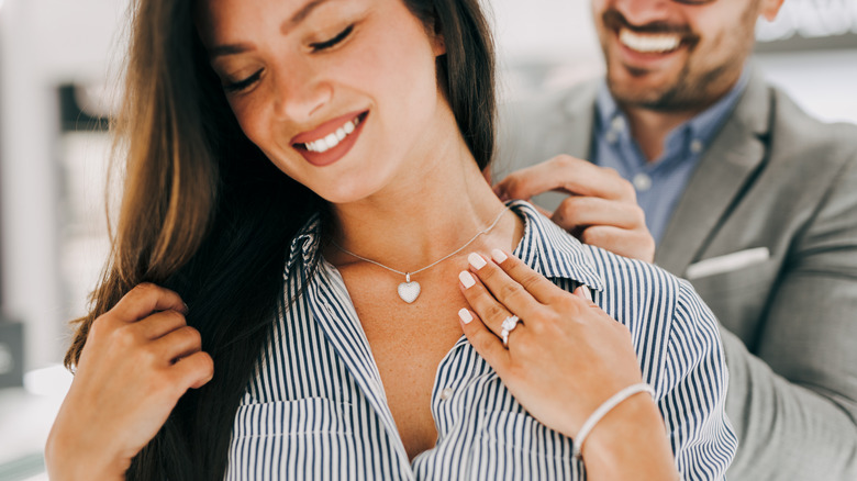 Woman smiling while a man puts a necklace on her