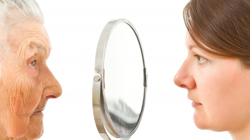 Older woman seeing younger one in mirror