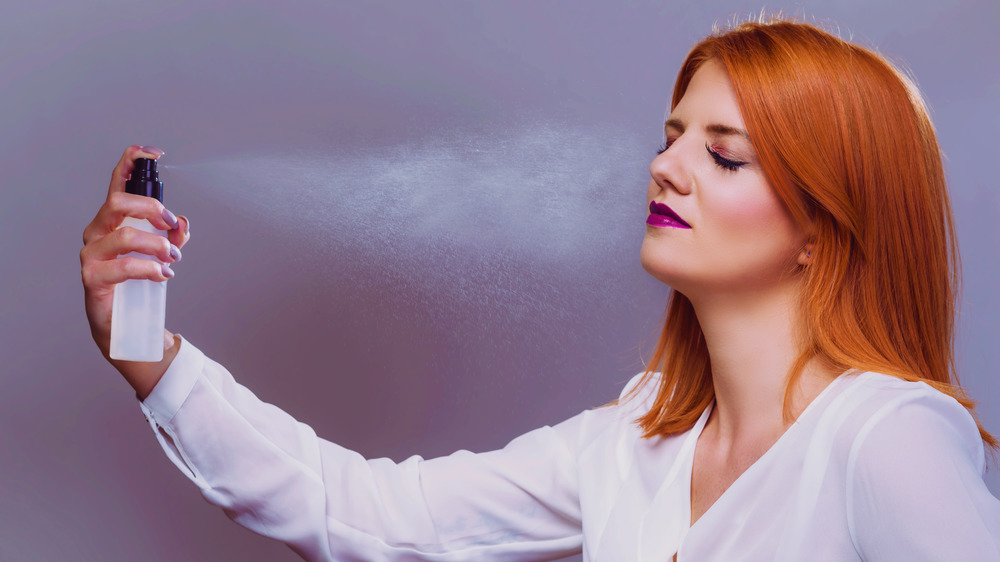 red haired woman spritzing her face