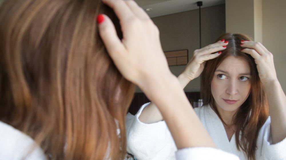 Woman examining scalp