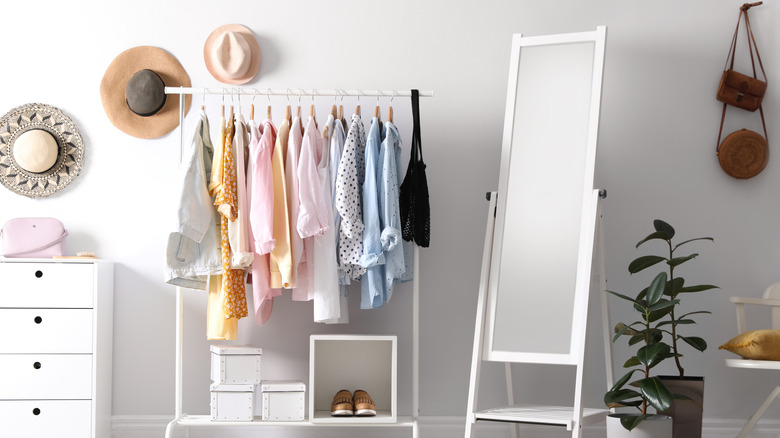 Room with a clothes rack, hats, shoes, and bags
