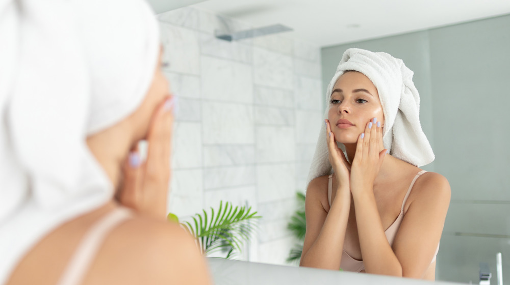 Woman applying face skin care