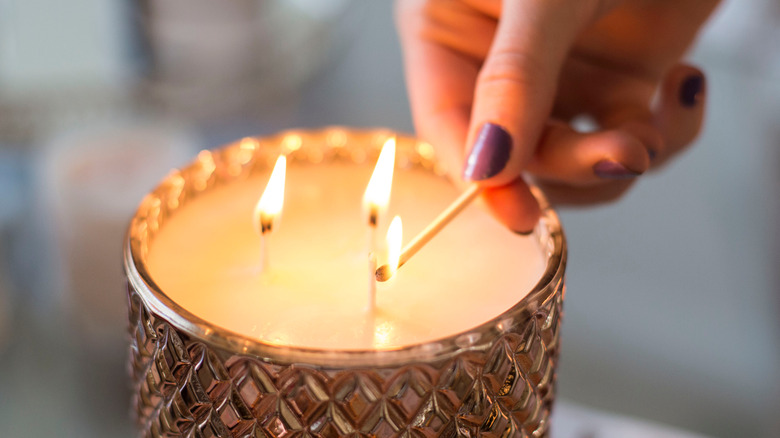 Woman lighting candle with a match