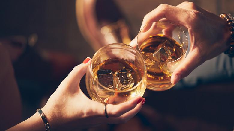 Couple drinking bourbon toasting