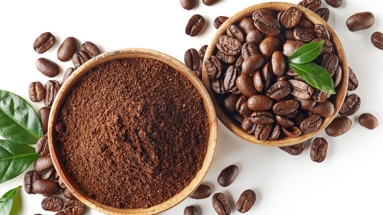 Cups of ground and whole coffee beans