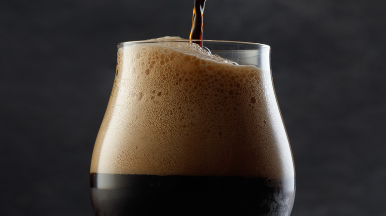 Dark beer pouring in a glass lots of foam
