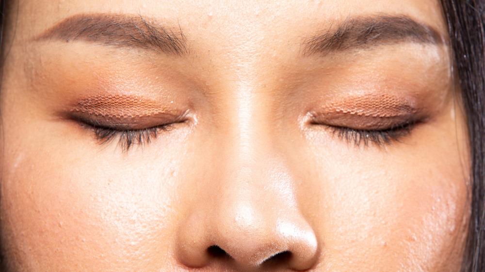Black-haired girl wearing eyelid tape