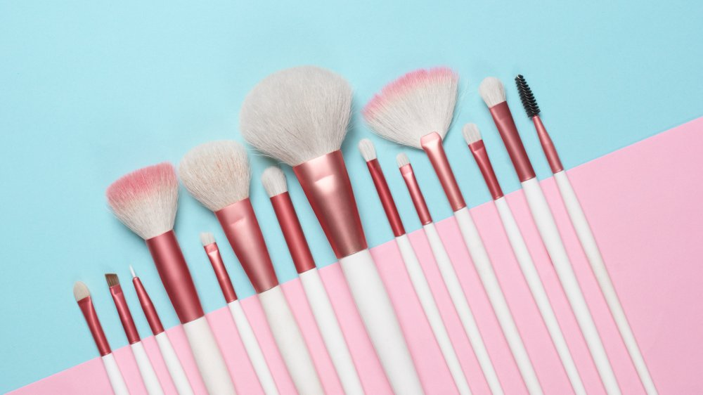 makeup brushes against a pale blue and pink background