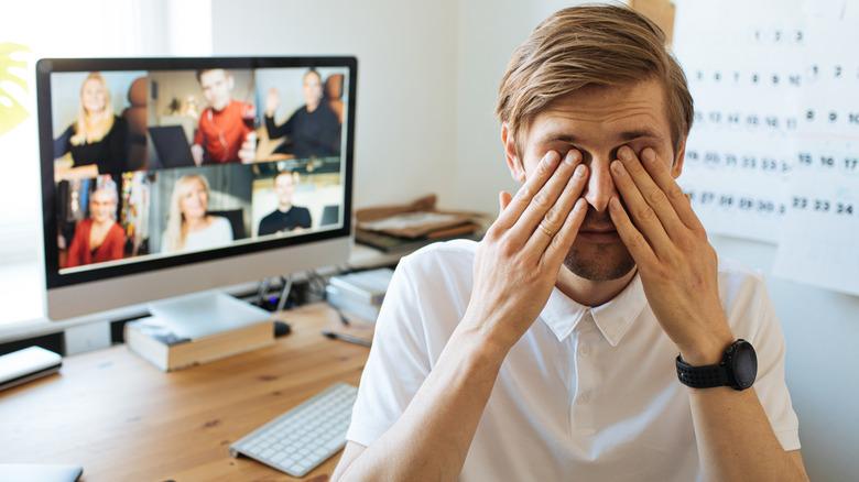 Man rubbing eyes during Zoom call